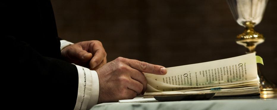 en præst bladrer i alterbogen