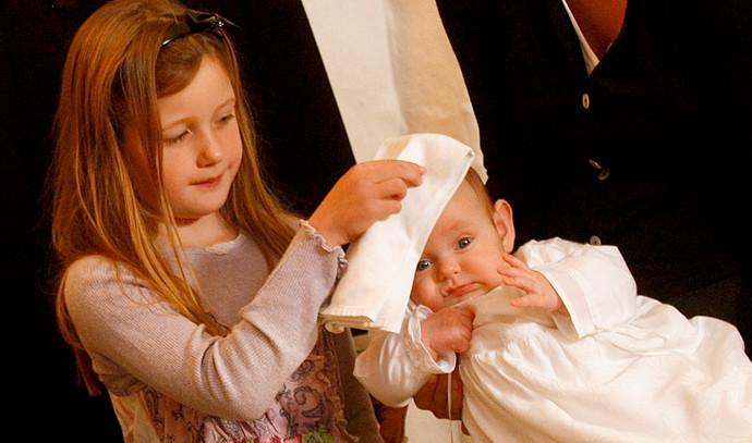 Pige tørrer dåbsbarns hoved
