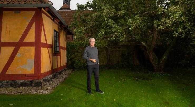 Peter Birch står i haven ved bispegården med et æble i hånden
